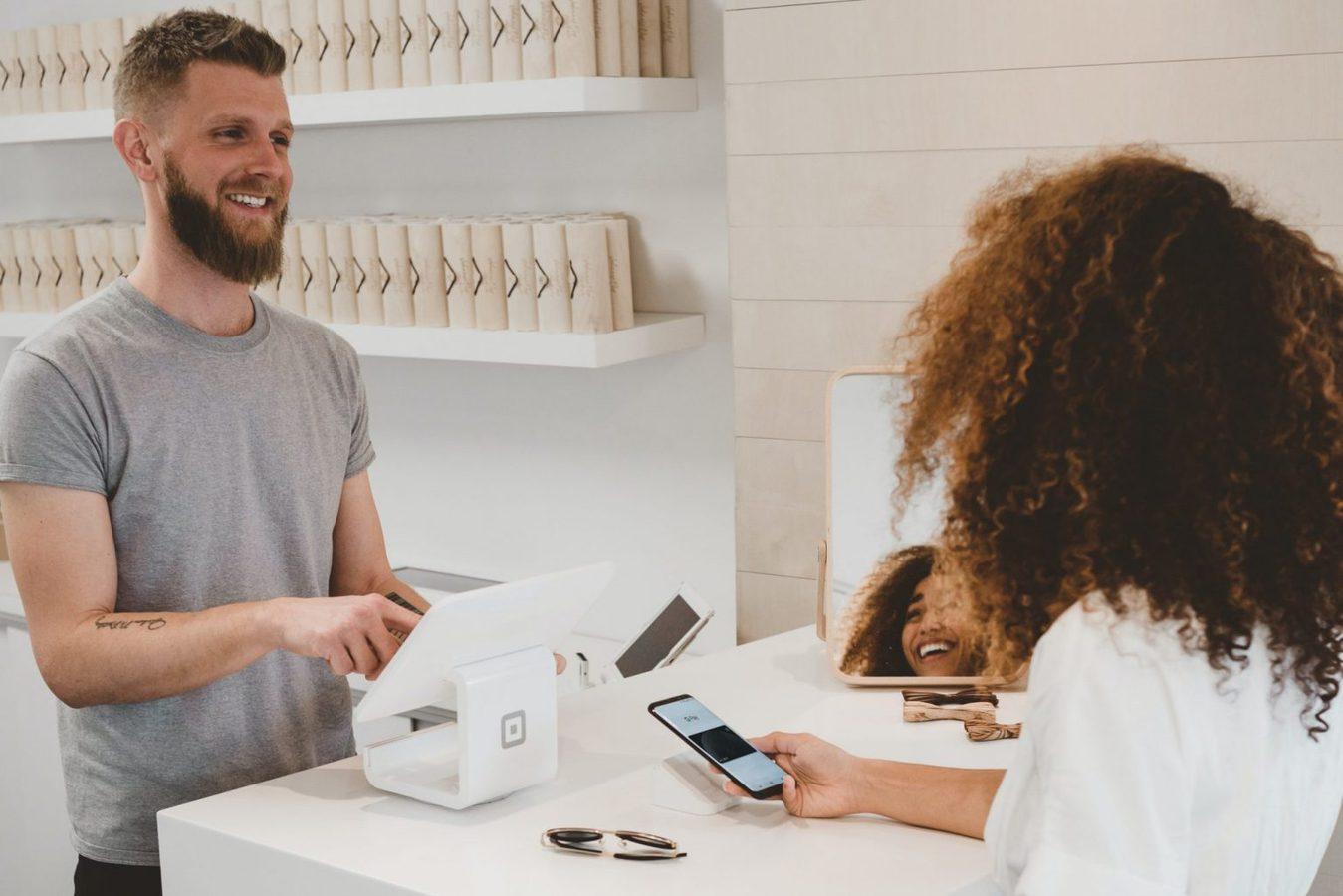 Uomo che serve una donna a un registratore di cassa in un negozio