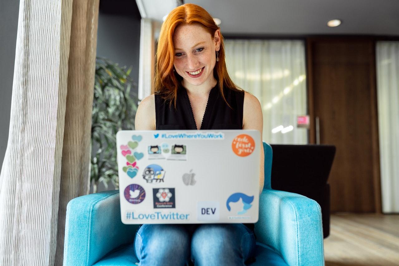 Een vrouw die met een laptop in een zwarte tanktop in een leunstoel werkt