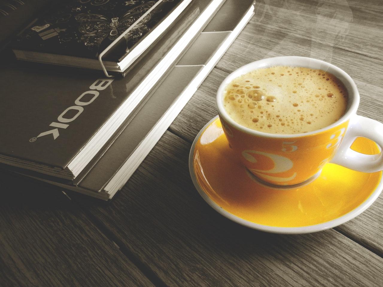Xícara de café amarela e livros sobre uma mesa de madeira