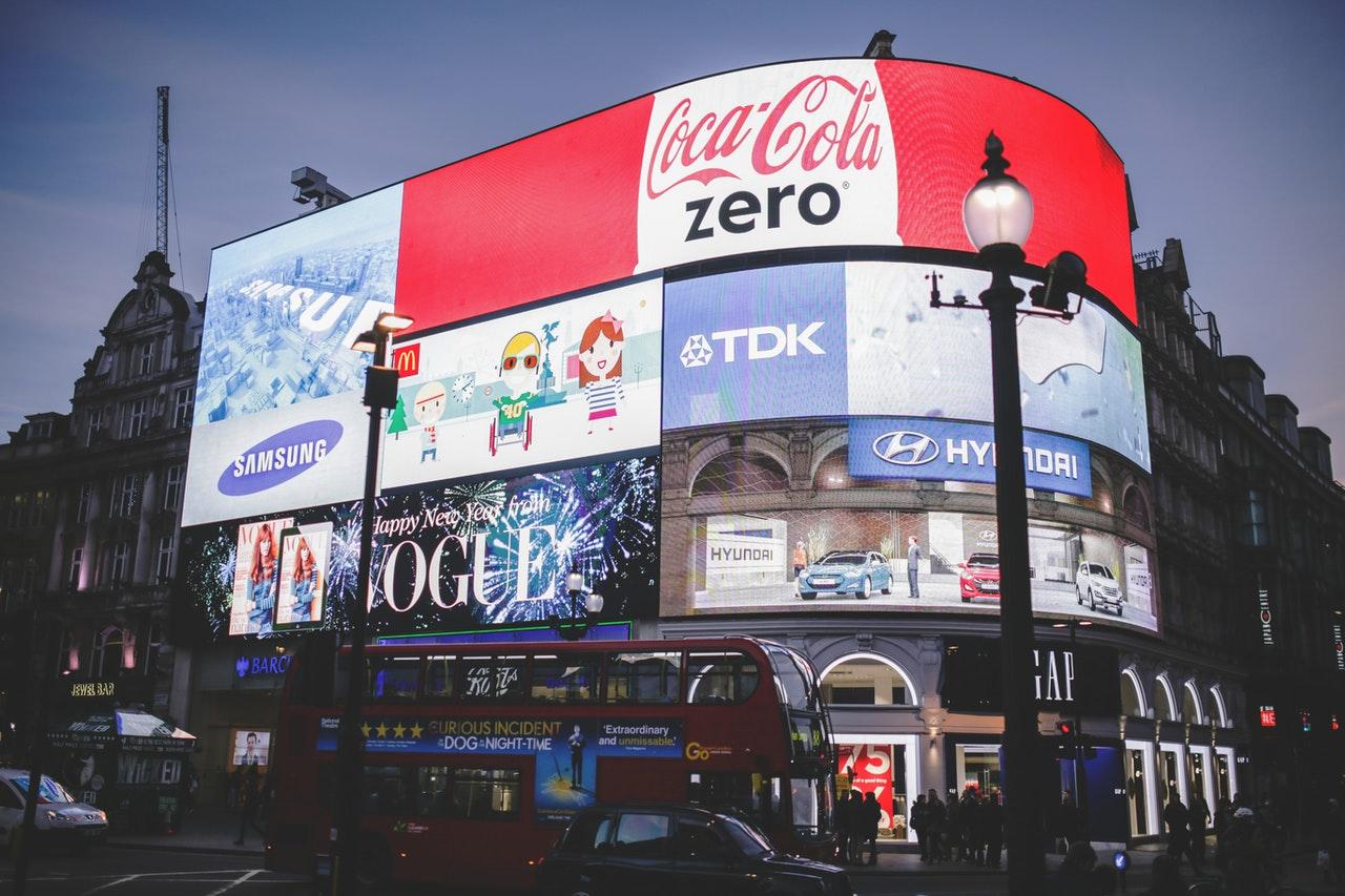 Annunci su Piccadilly Circus con un cielo grigio sul retro
