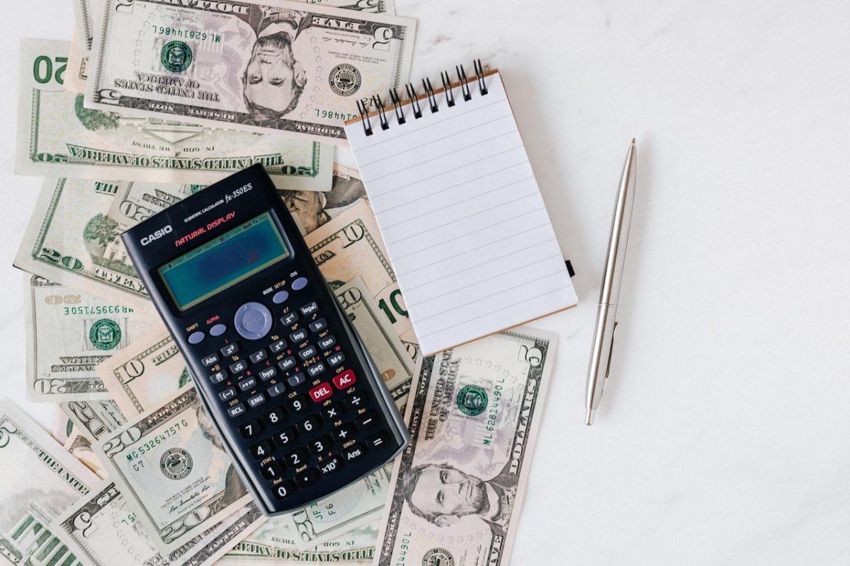 Dinheiro, calculadora, caneta e bloco de anotações sobre uma mesa branca
