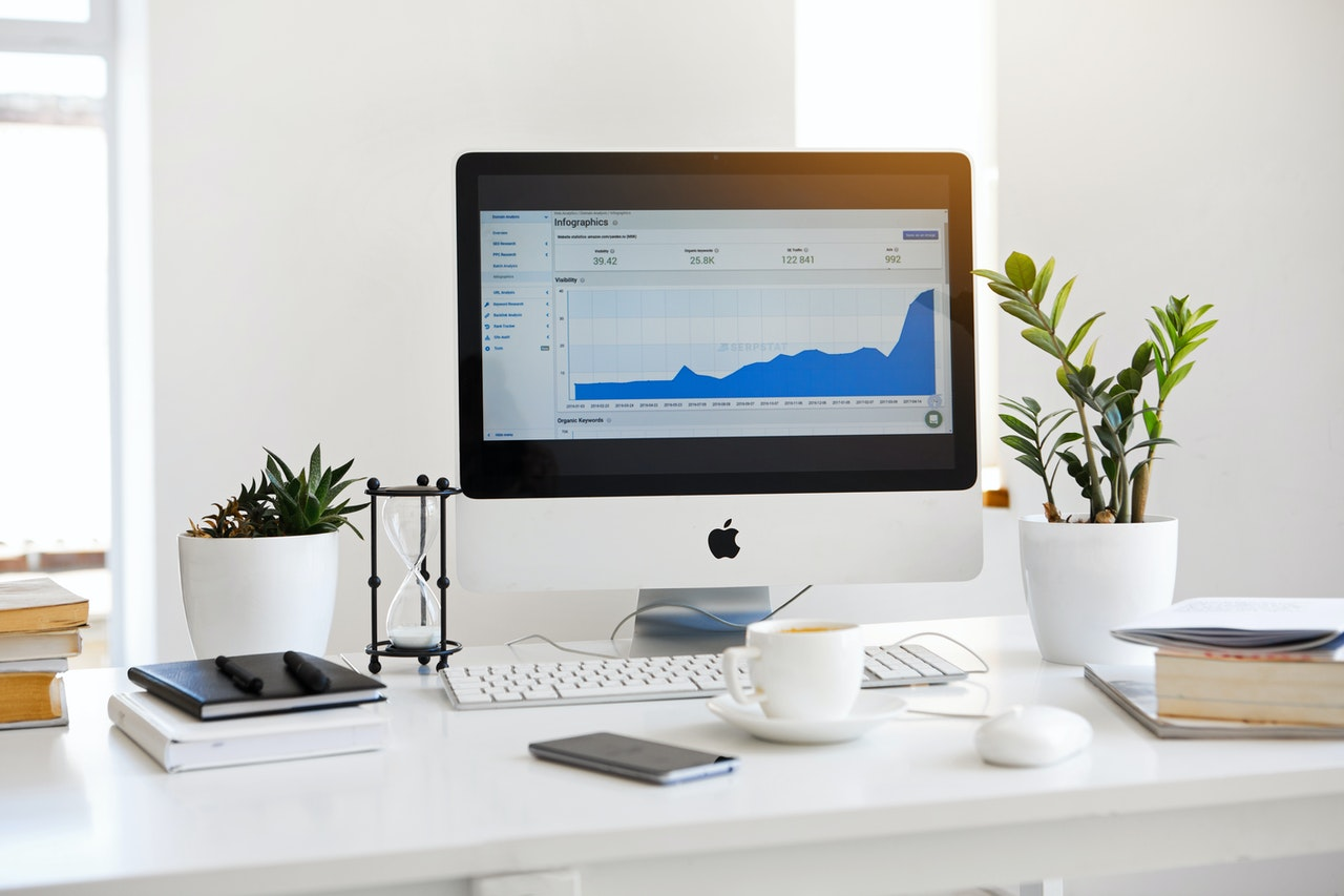 Computer con statistiche sullo schermo in una stanza bianca