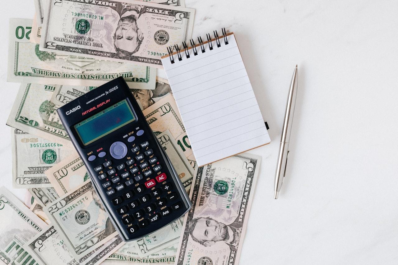 Geld, rekenmachine, notitieboekje en een pen op een wit bureau