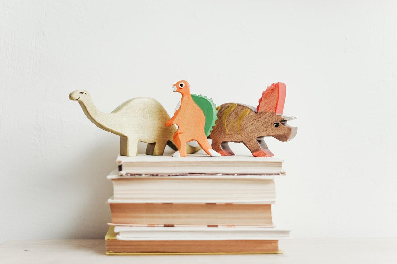 Dinosauri in legno su una pila di libri su uno sfondo bianco
