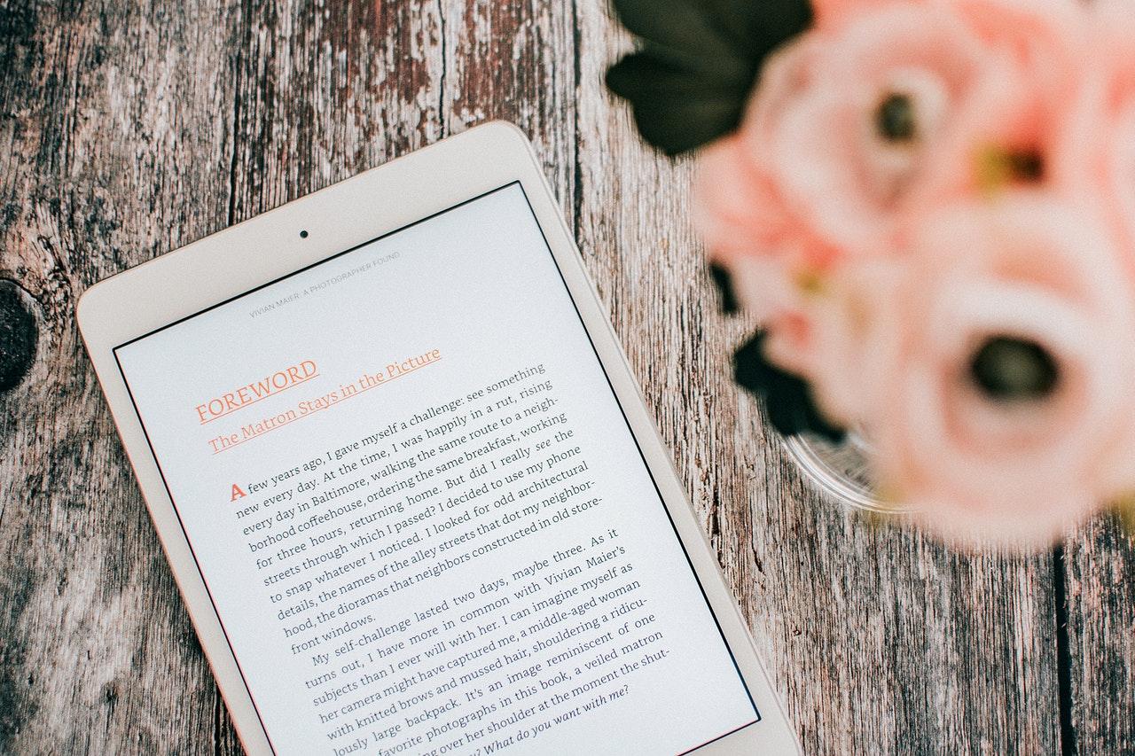 Een e-boek zichtbaar op een reader op een houten tafel met bloemen erop