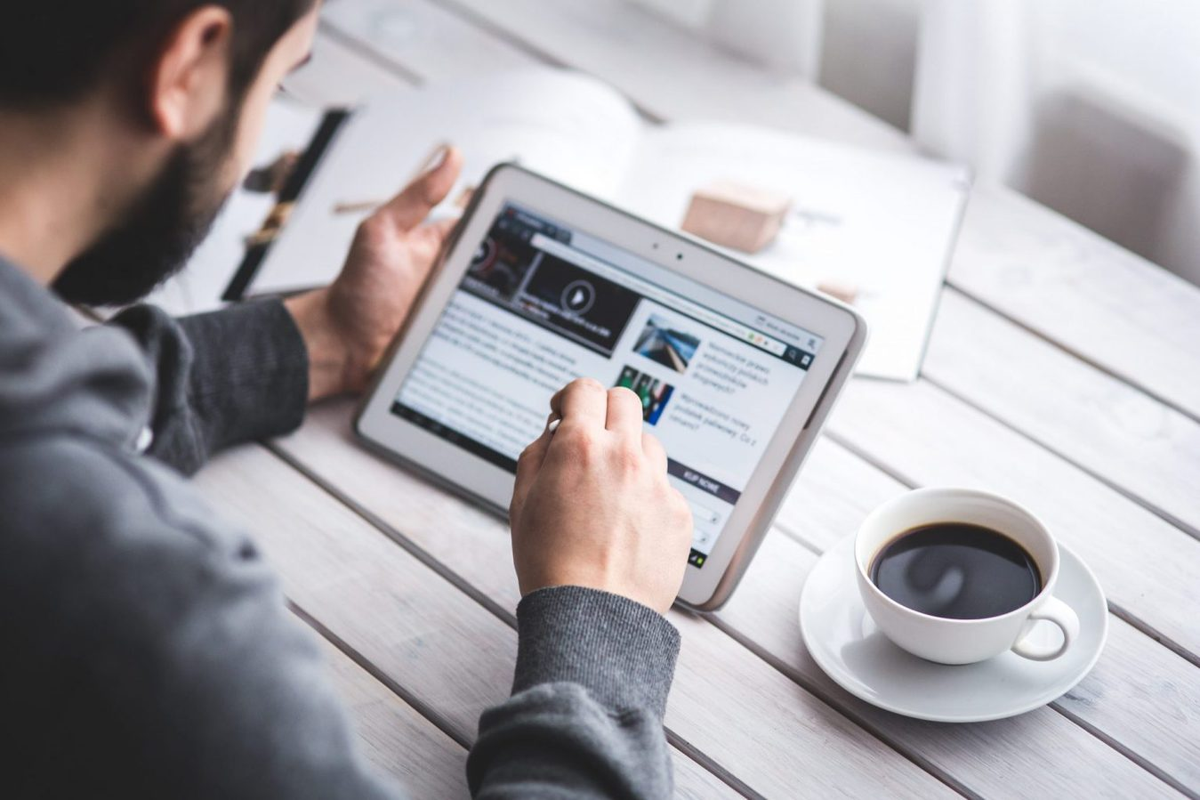man met kopje koffie leest het nieuws op ipad