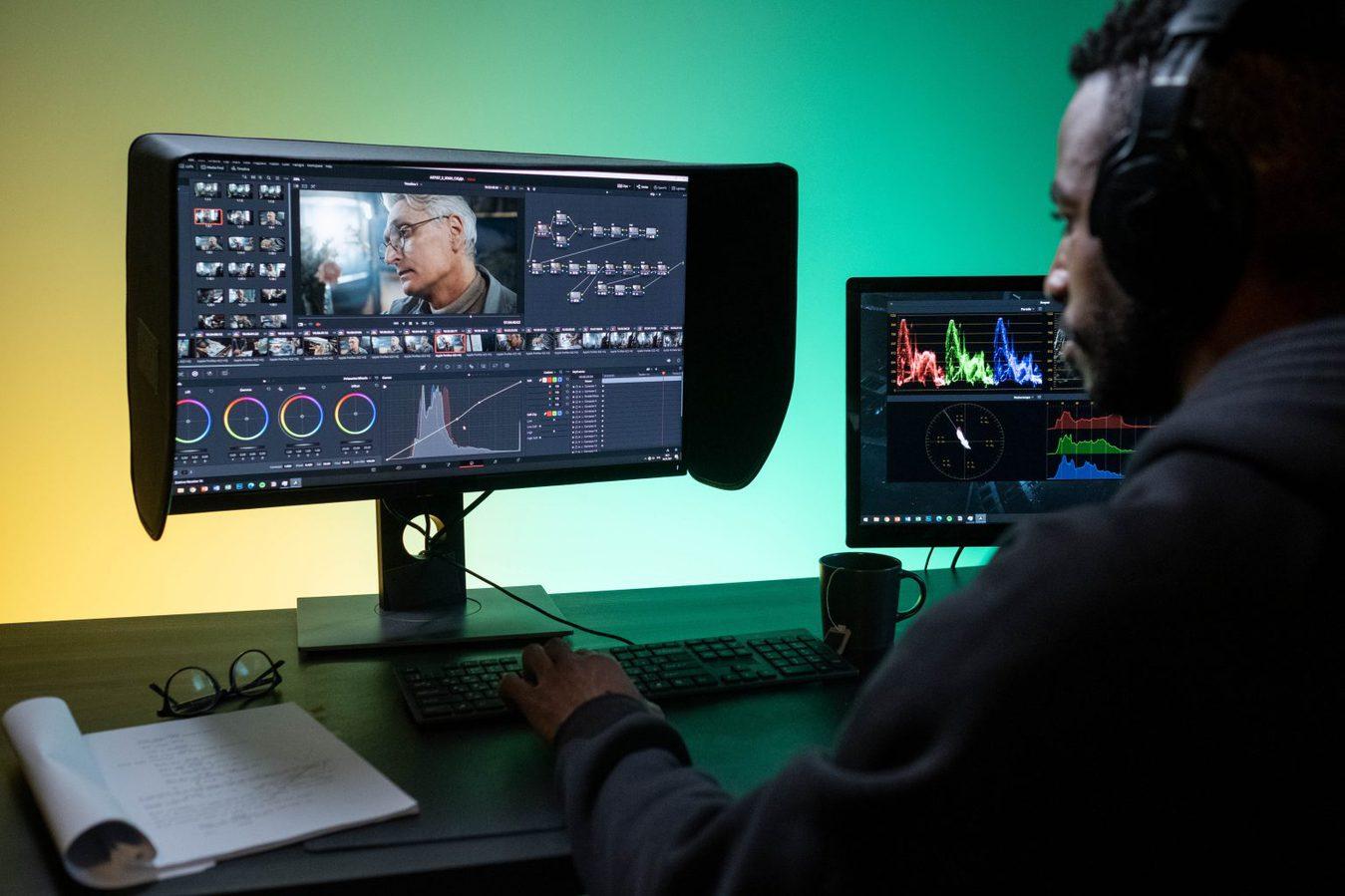 man sitting at desk using editing software
