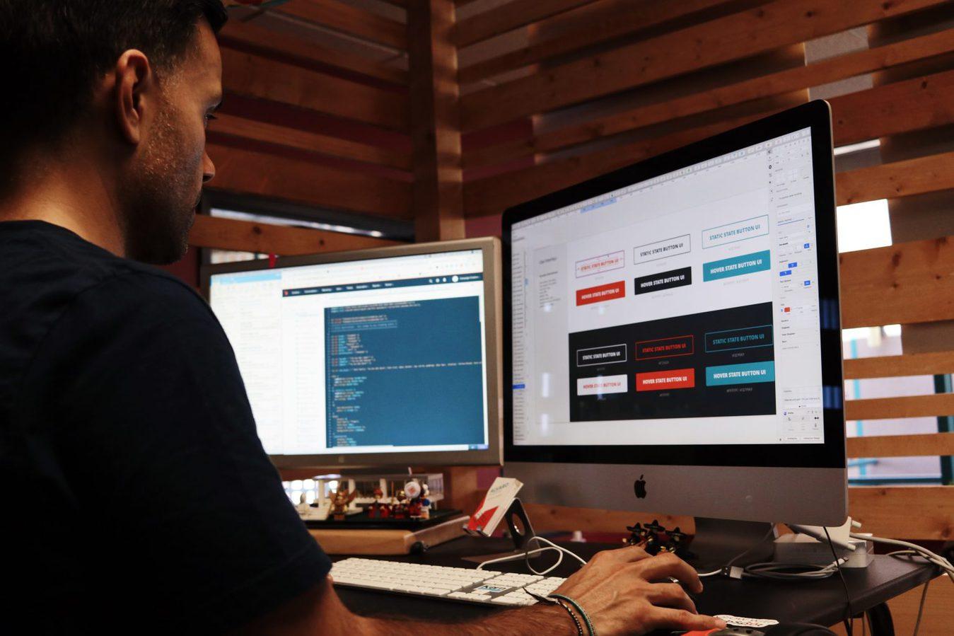 hombre sentado en el escritorio frente a dos monitores de computadora