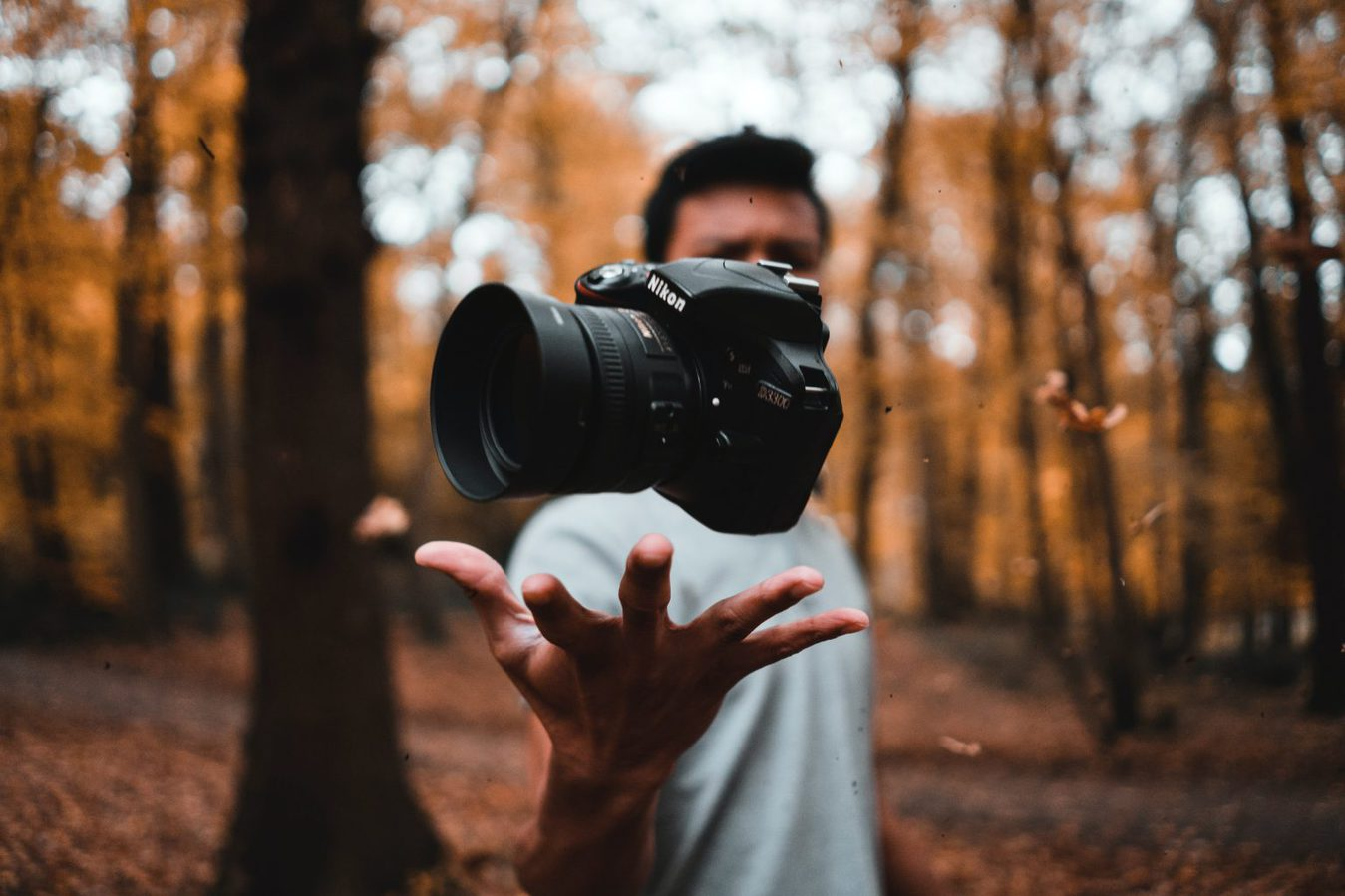 man standing in woods throwing camera in air