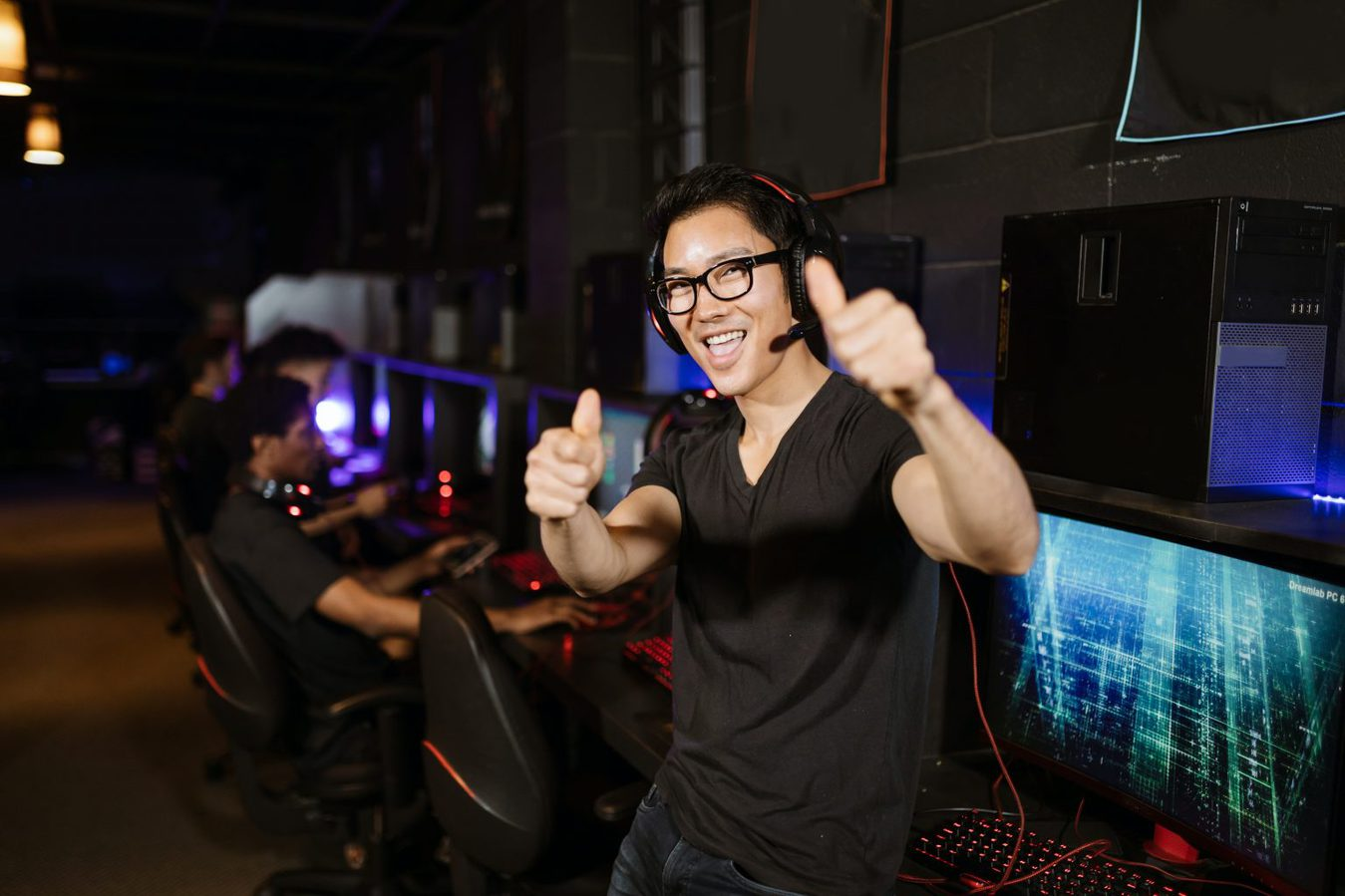 man wearing headset holding two thumbs up