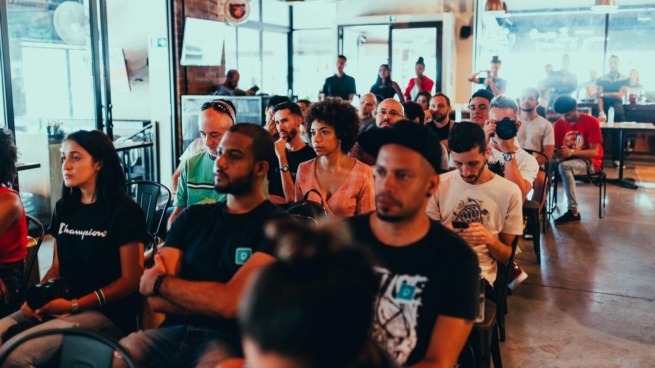 Mensen die tijdens een evenement binnen op stoelen zitten
