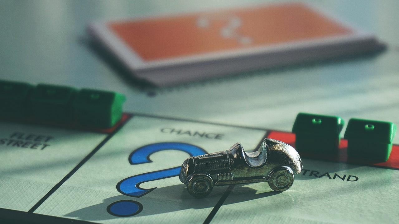 Een Monopoly bord met een auto en huizen naast een stapel kaarten