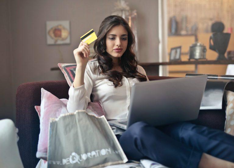 Mulher sentada no sofá olhando para o notebook, com um cartão de crédito na mão e sacolas de compras ao redor