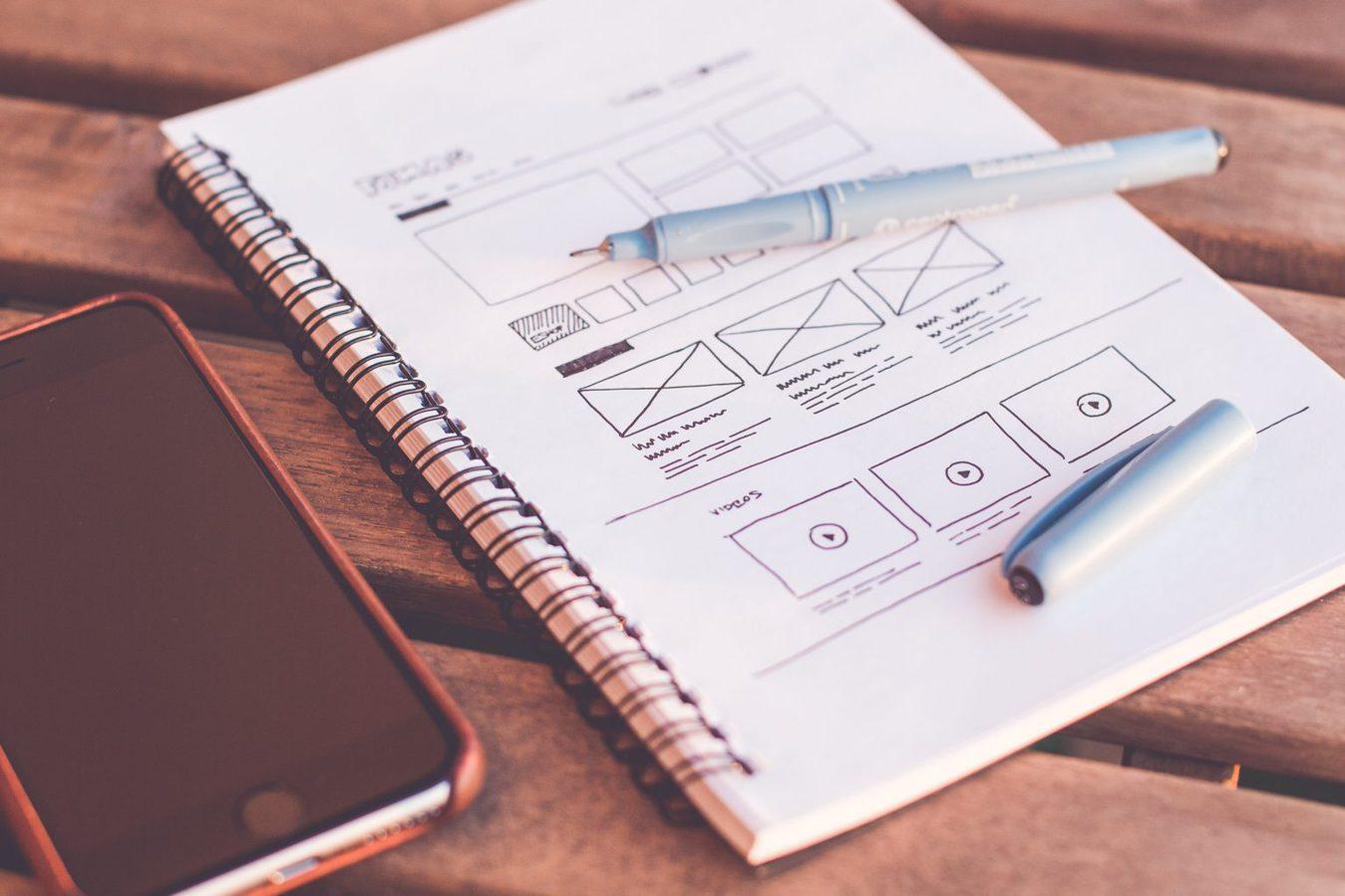Bloc de notas con bocetos de diseño web y bolígrafo encima