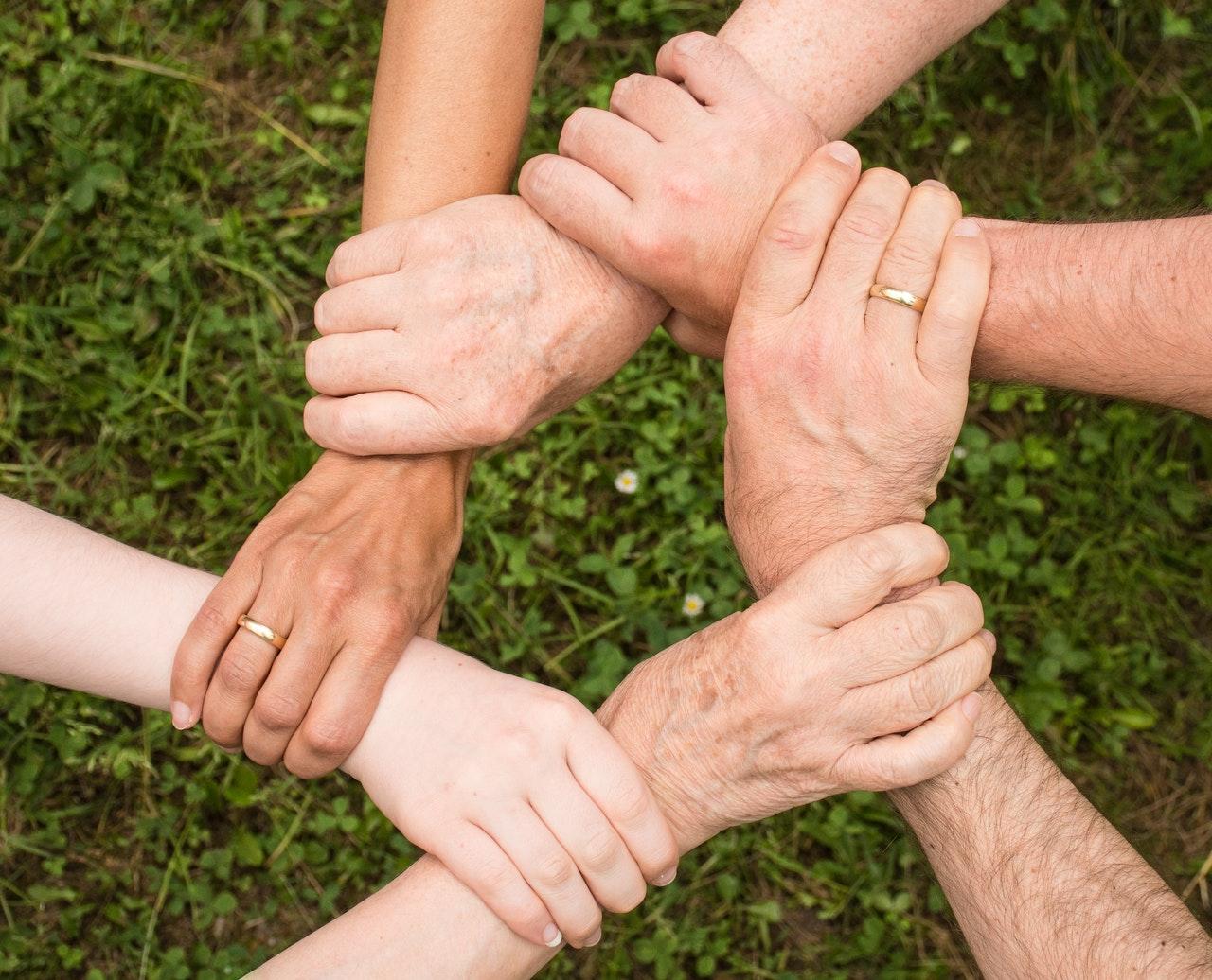 Persone che si stringono le mani in cerchio all'aperto