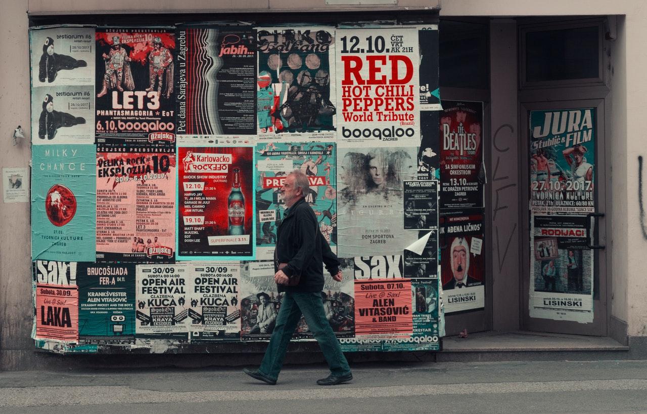Een persoon die op een stoep langs een muur met advertenties loopt