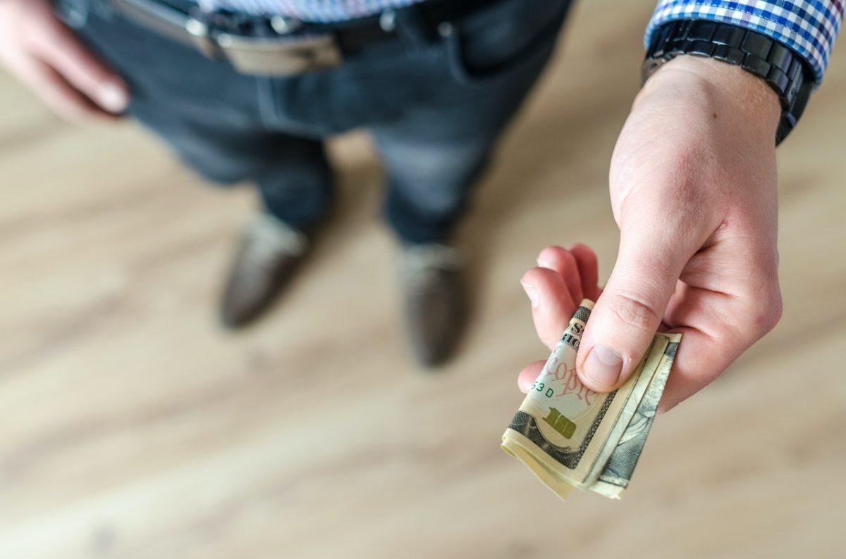 Pessoa entregando notas de dinheiro
