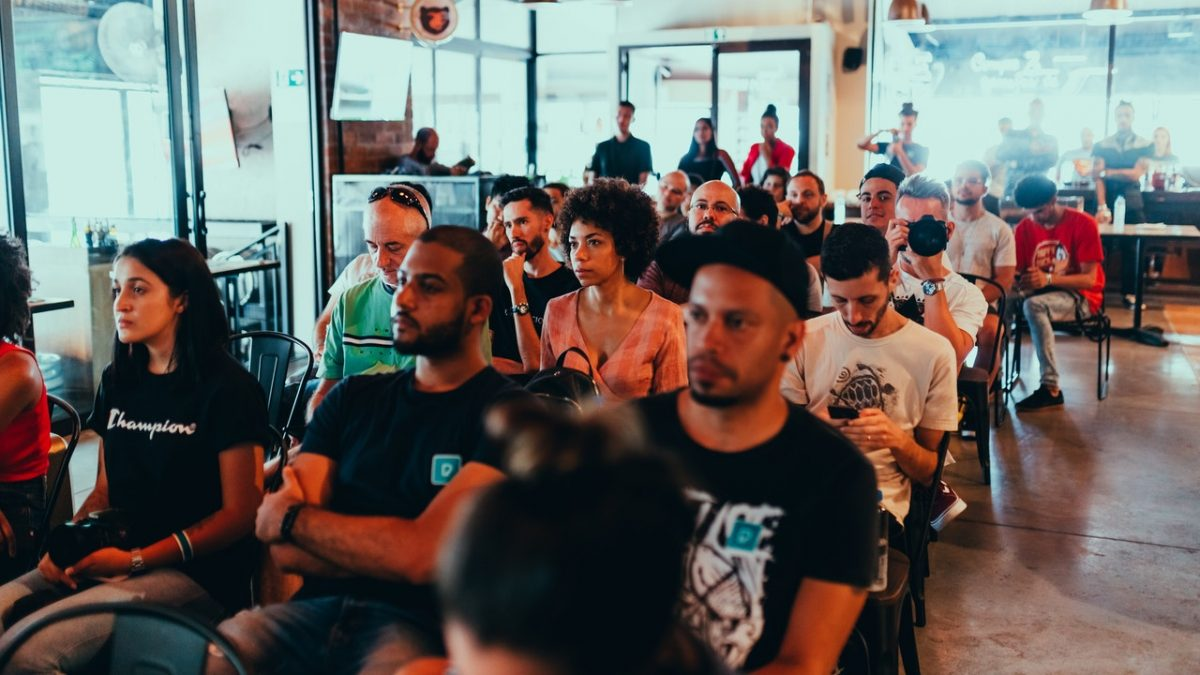 Pessoas sentadas em cadeiras assistindo a um evento