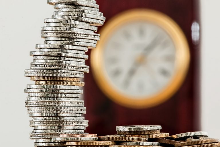 Pilha de moedas com um relógio no plano de funco