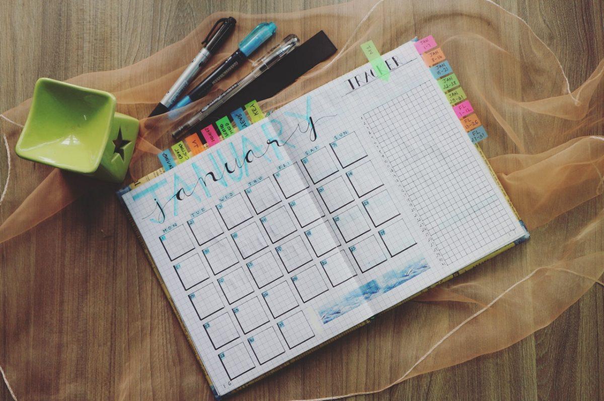 Planner com marcadores, aberto sobre uma mesa de madeira