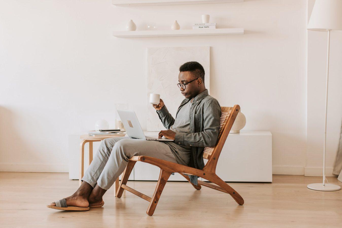 Pria duduk di sofa sambil menggunakan laptop