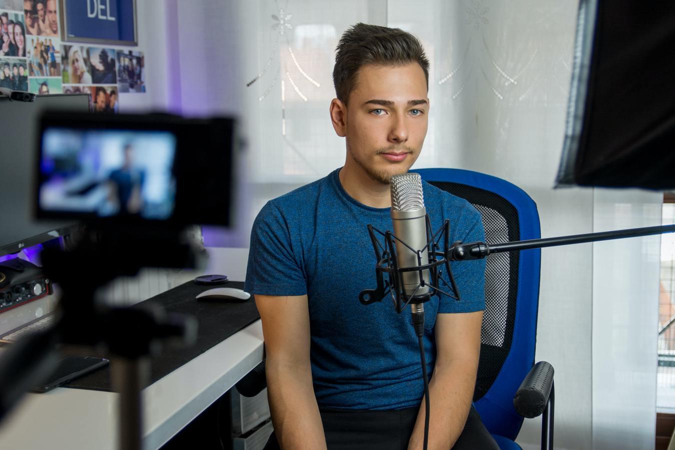 Registrazione di un video YouTube con un ragazzo con una videocamera e un microfono