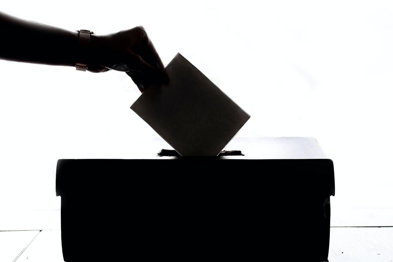 Un seggio elettorale in bianco e nero con una mano che inserisce una scheda
