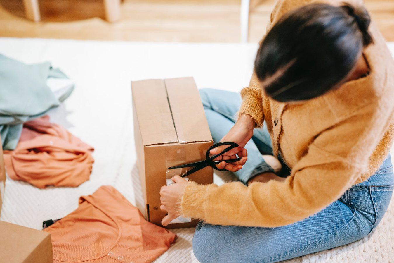 side shot of woman taping up cardboard box