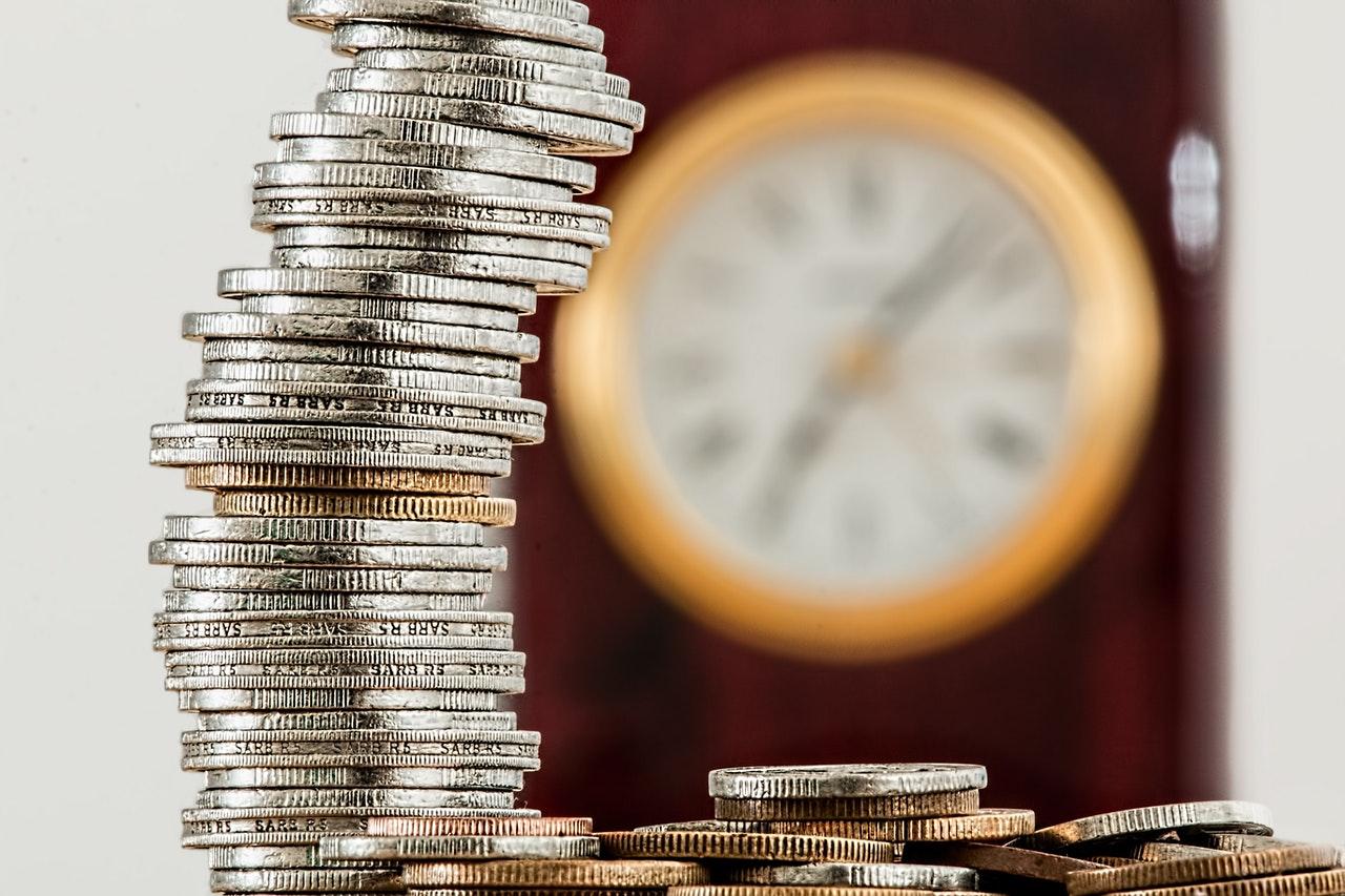 Een stapel munten met een klok op de achtergrond