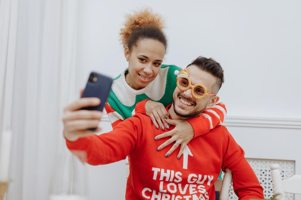 Two people in Christmas jumpers taking selfies