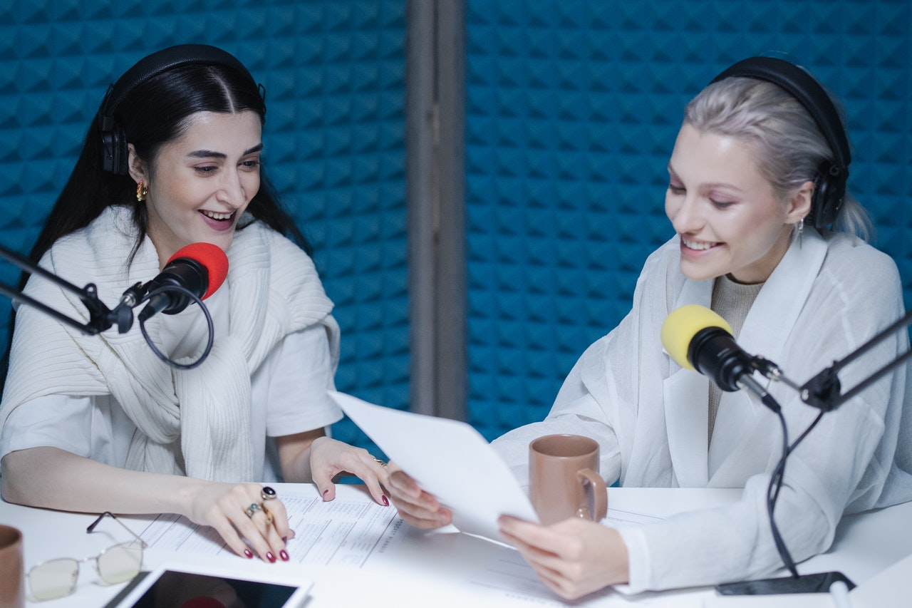Two women recording a podcast in a room with a blue wall