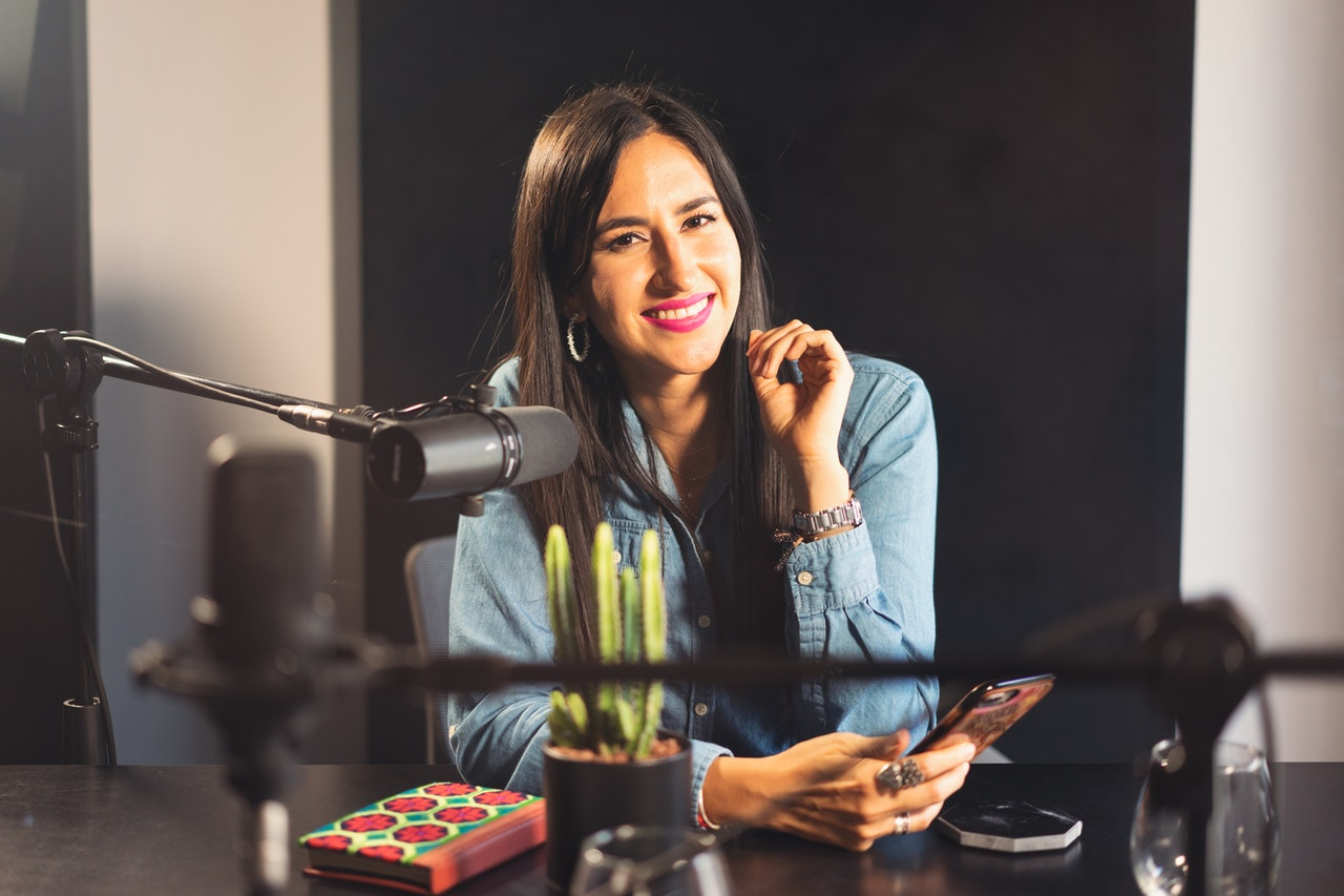 A woman smiling at a camera in a podcast recording booth
