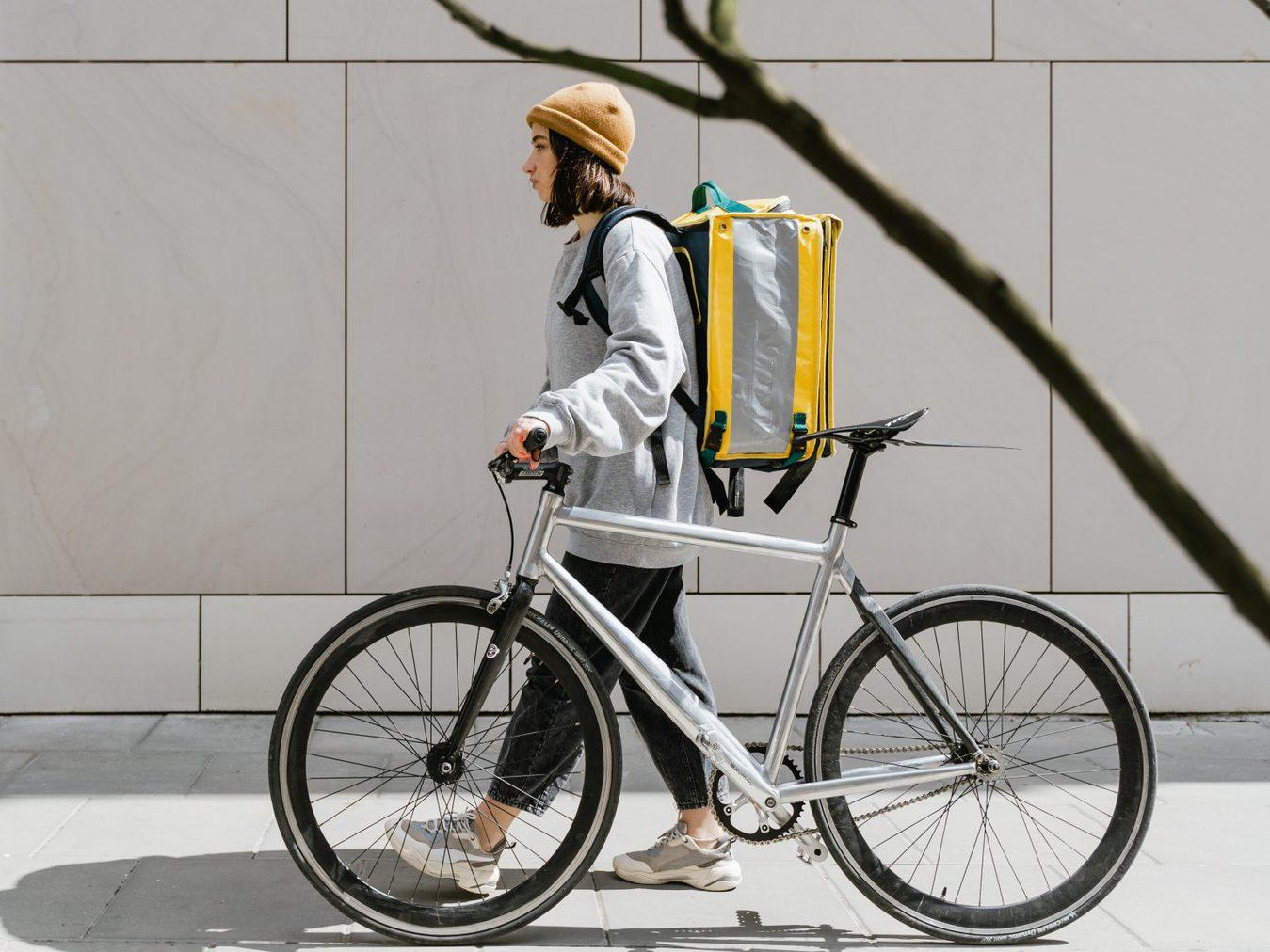 woman wheeling bike and wearing courier bag