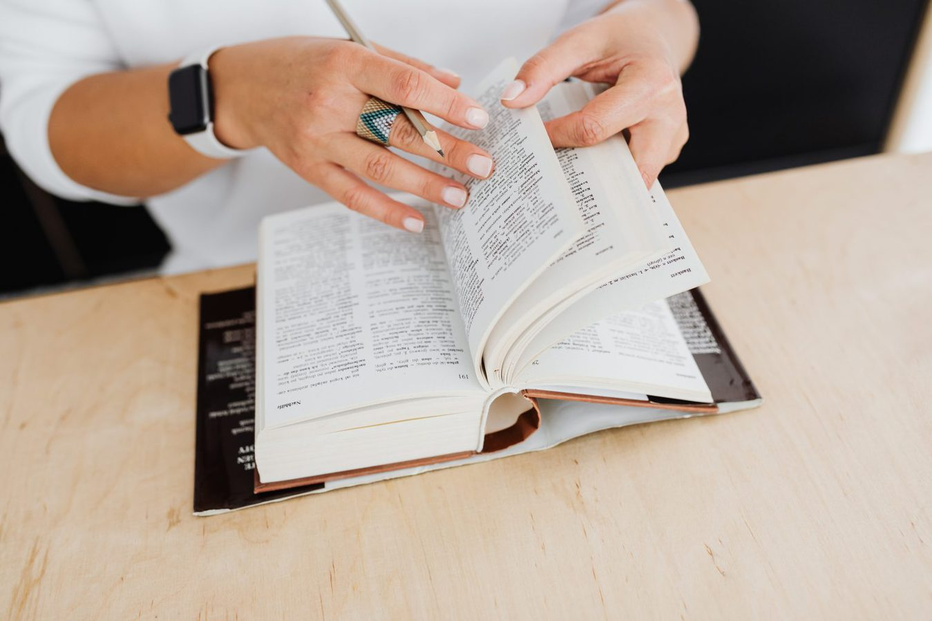 woman's hands flicking through dictionary