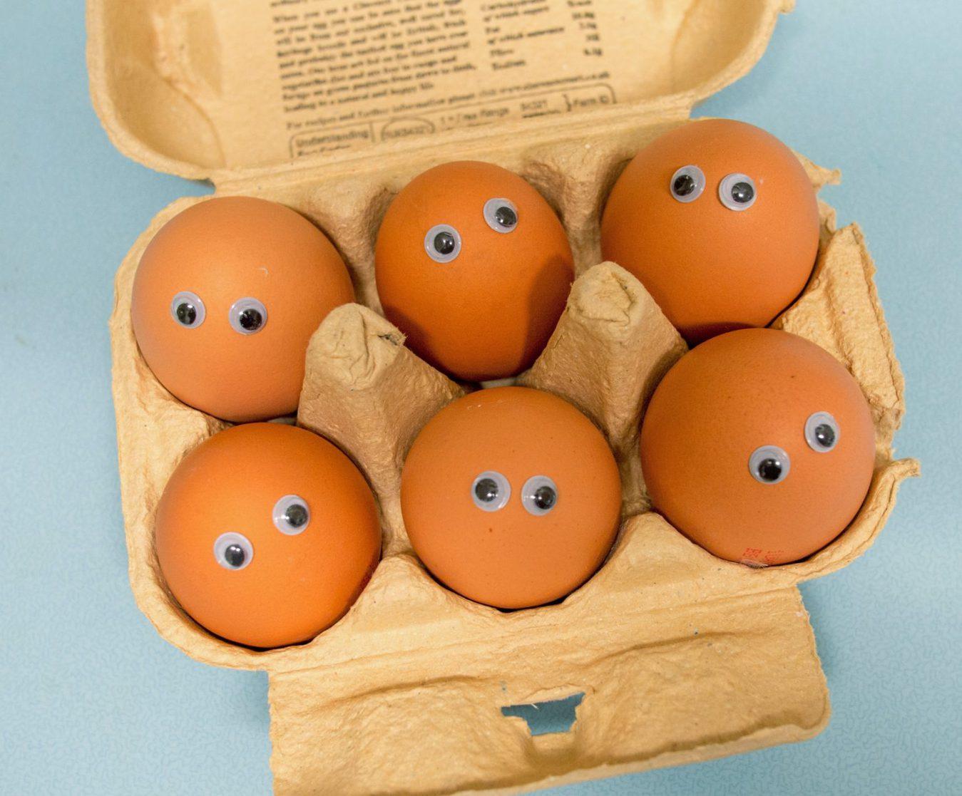 Jajka z oczami w pudełku na niebieskim tle