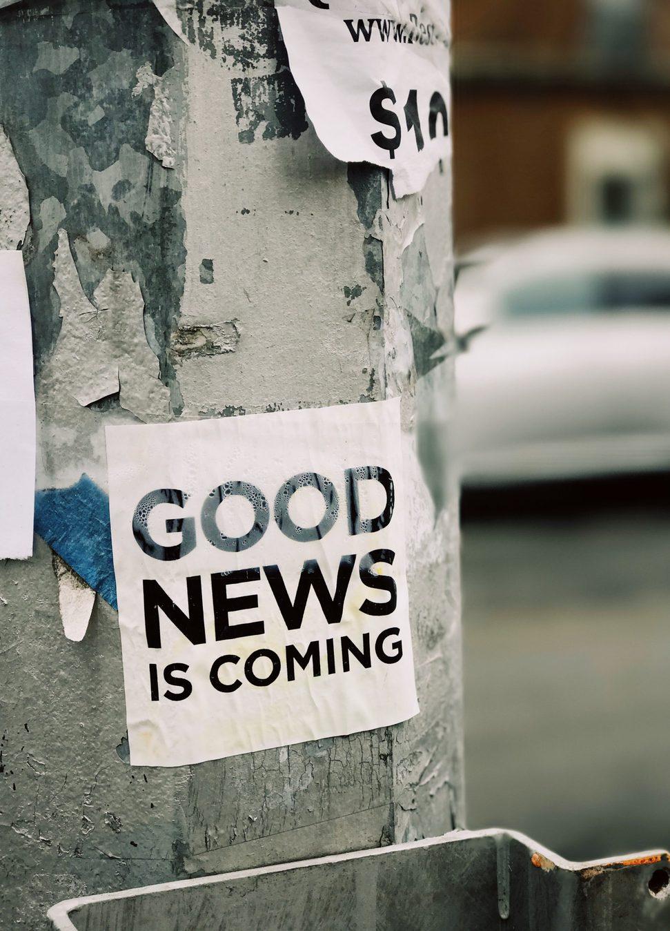 """Papel colado no post com os dizeres """"Boas notícias vêm aí"""", em inglês"""