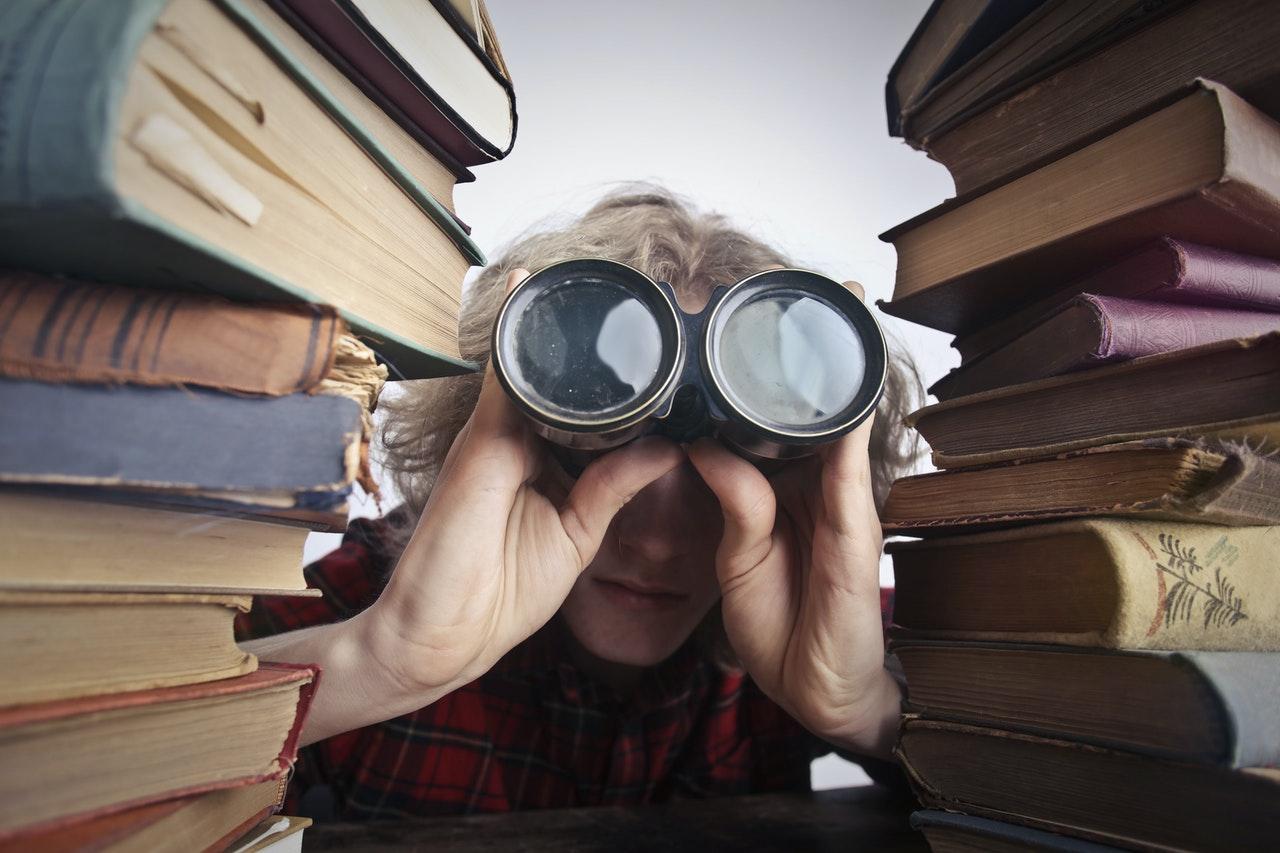 Een man met verrekijker tussen twee stapels boeken