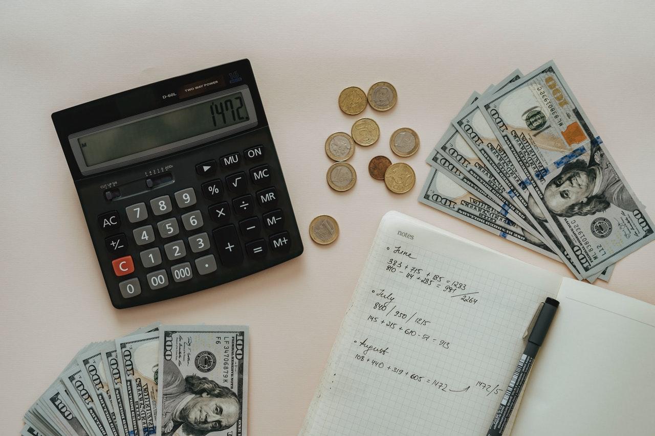 Soldi, calcolatrice, notebook e penna su un tavolo bianco