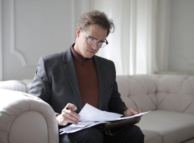 Homem de terno sentado no sofá e lendo documentos