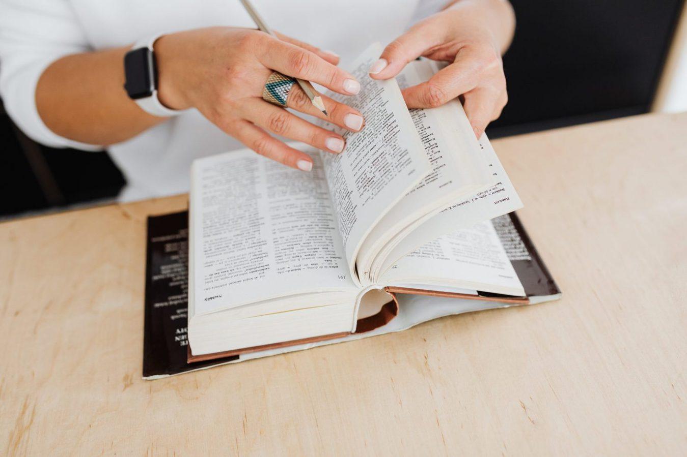 Mani di una donna che sfoglia un dizionario