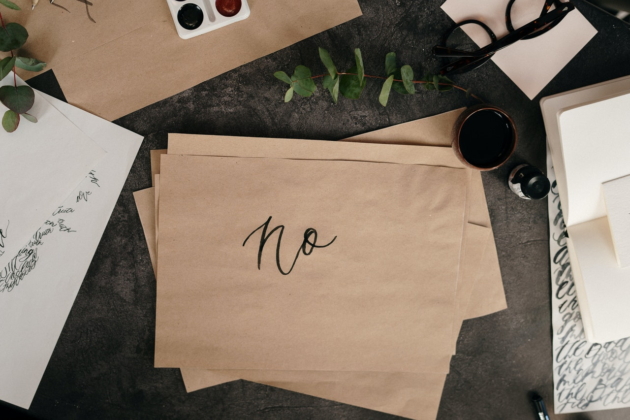 Papers on a desk with a handwritten note spelling out no