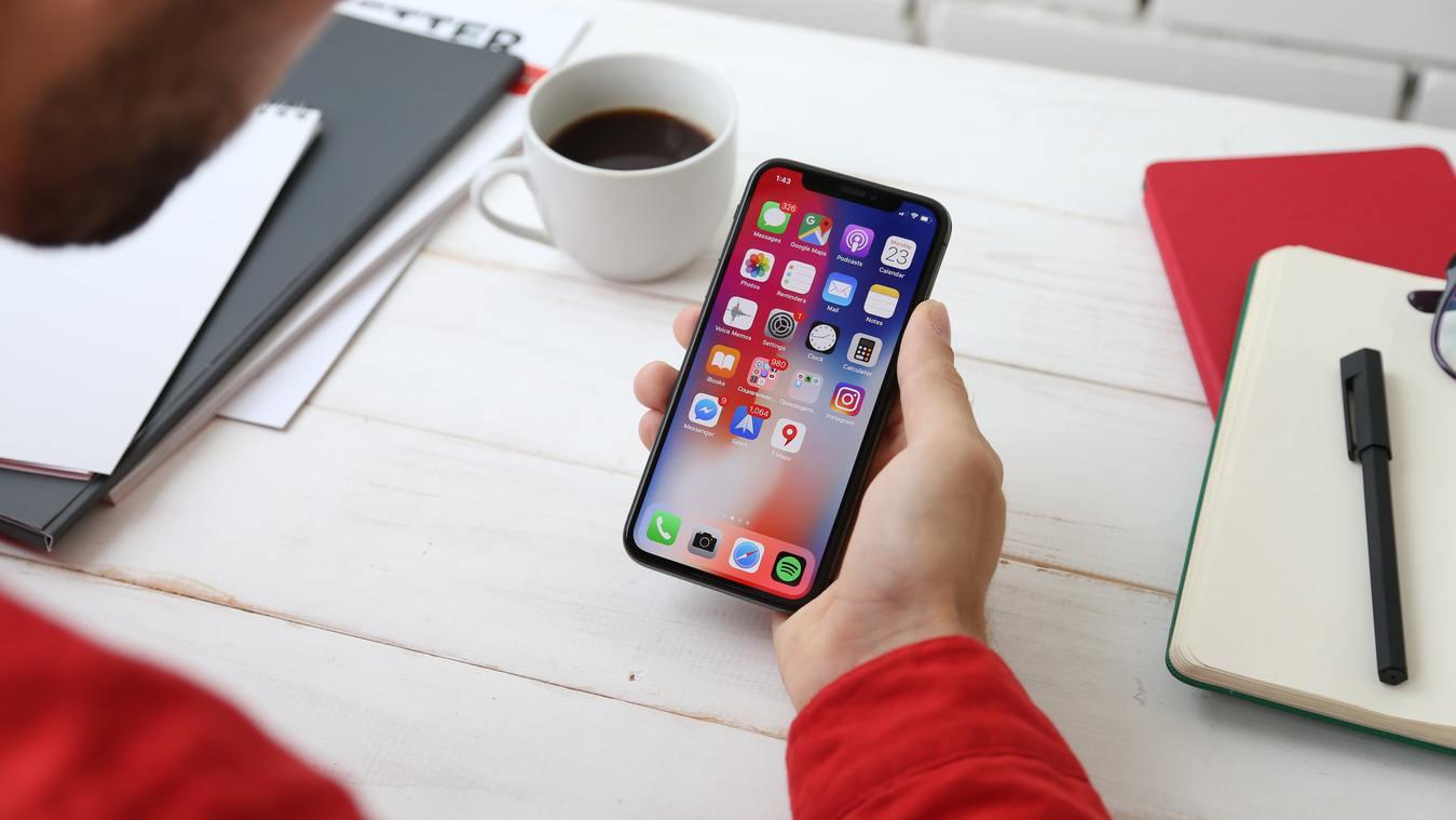 Persona che tiene in mano un cellulare su un tavolo bianco
