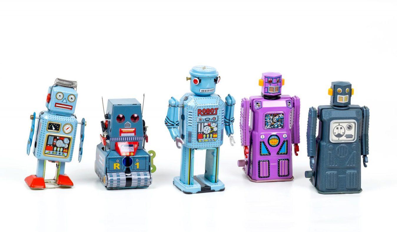Piccoli robot giocattolo in fila su uno sfondo bianco