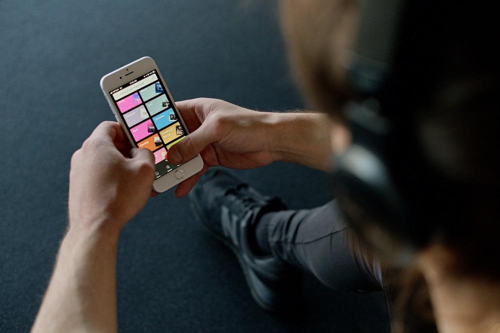 Scatto dall'alto di una persona che scrolla attraverso Spotify sul suo cellulare