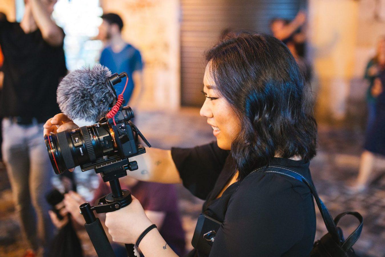Scatto laterale di una donna che tiene e punta una fotocamera