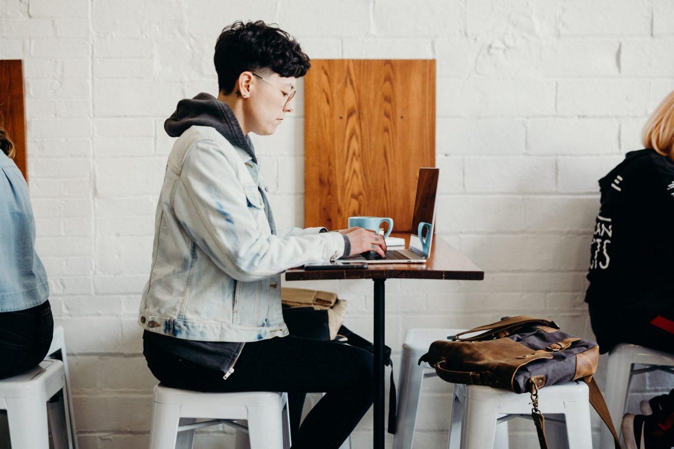 Scatto laterale di una persona seduta su uno sgabello in un bar con un laptop
