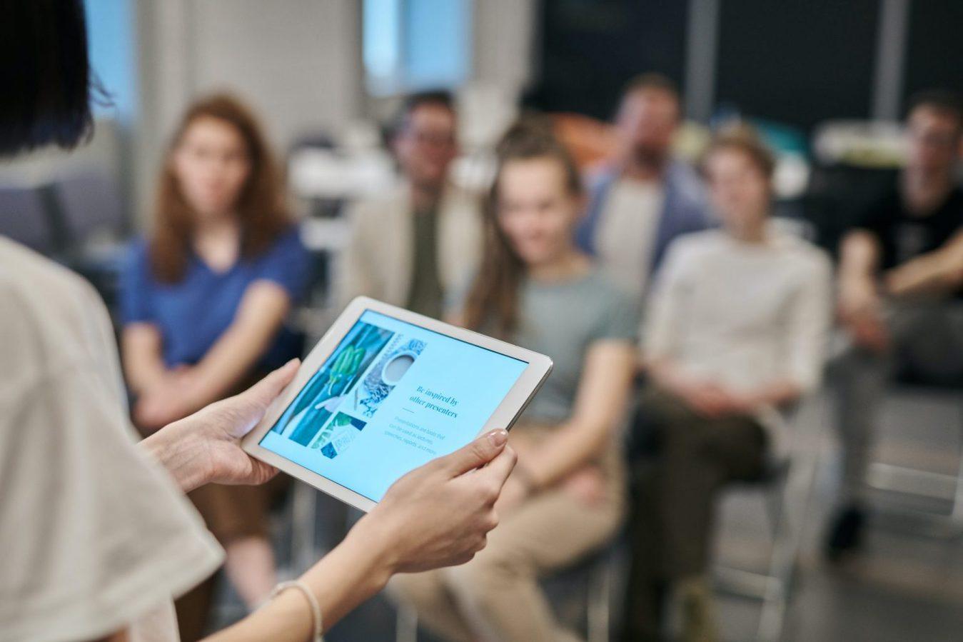 Scatto laterale di una persona che tiene un iPad in mano davanti una classe di studenti