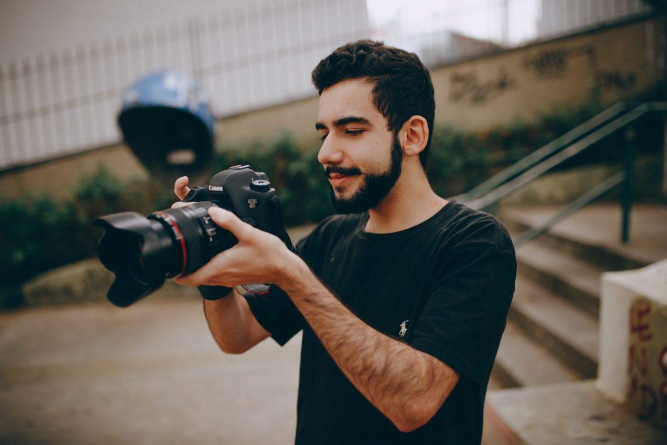 Scatto laterale di un uomo che tiene e punta una fotocamera