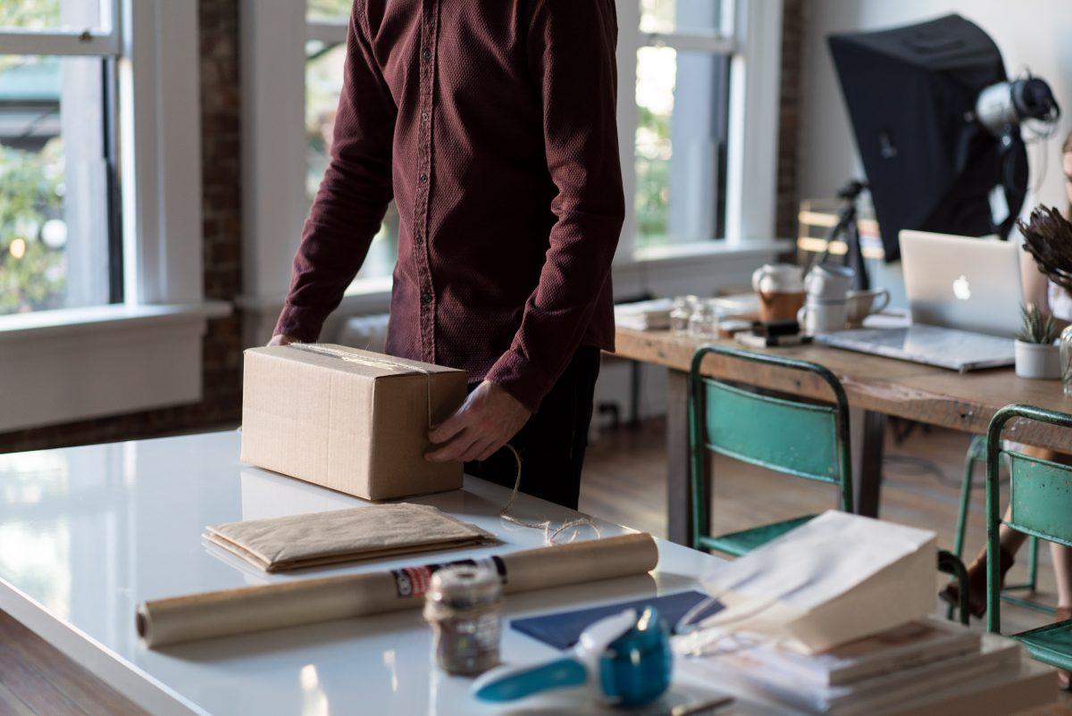 Uomo che chiude una scatola di cartone con del nastro su un tavolo