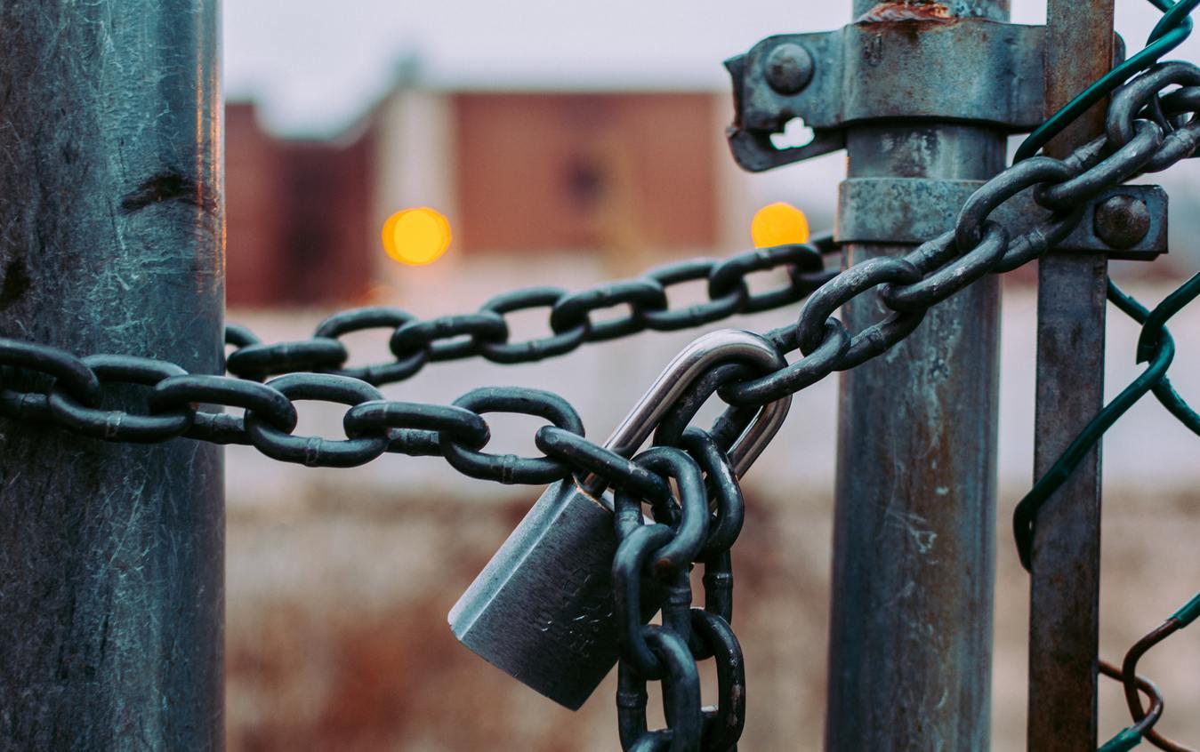 Cadeado pendurado em corrente, trancando portão